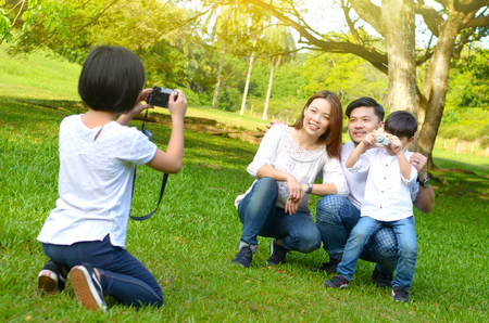 Asian family taking photo in the park