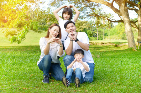 Outdoor portrait of beautiful asian family making love shape with hands Stock Photo