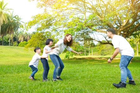 Asian family playing game of eagle, hen and chicks in the park