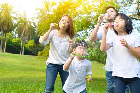 Famiglia asiatica che soffia bolle nel parco