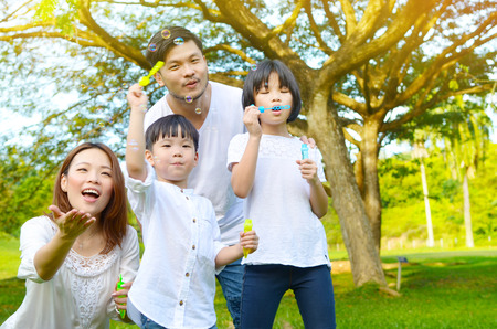 Happy asian family blowing bubbles in the park