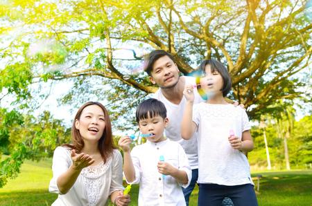 Famiglia asiatica che soffia bolle nel parco Archivio Fotografico
