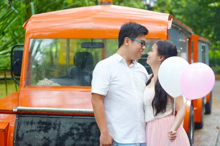 Asian girl holding balloons and looking at her boyfriend