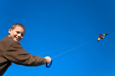 Boy flying a kite with clear blue sky photo