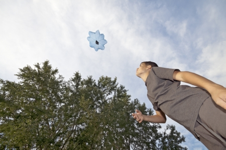 raised viewpoint: Boy playing with parachute toy, view from below Stock Photo