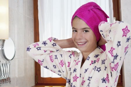 Young woman in bath robe and towel on head in bright bathroom photo