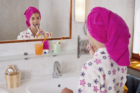 Young woman brushing teeth in bath robe with towel on head in bright bathroom photo