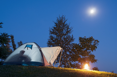 Camping in tent with human shadow and campfire, moon and stars on the clear blue sky photo