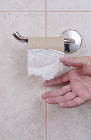 toilet paper: Empty toilet paper holder in a bathroom with hand