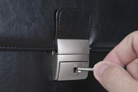 black briefcase: Bloqueo Malet�n negro con la mano y la llave Foto de archivo