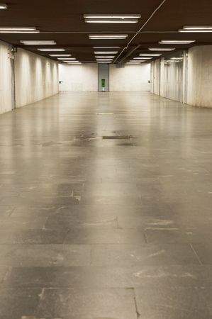 underpass: Empty underpass with lights and grey tiled