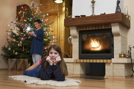 Young woman and man front of fireplace with Christmas tree in background photo