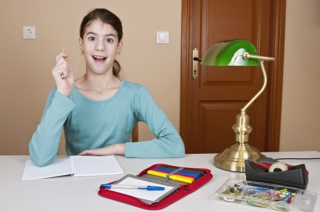 invented: Young woman invented big idea at desk with workbook and pencil Stock Photo