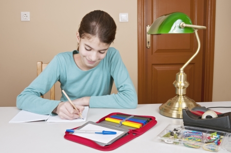 workbook: Writing young woman at desk with workbook and pencil Stock Photo
