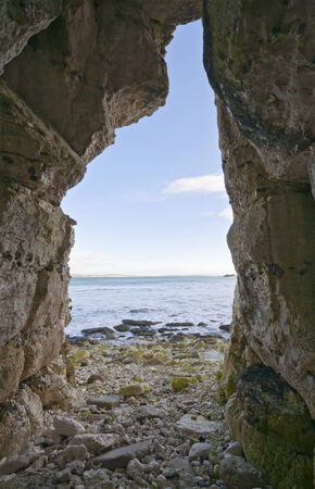 Lookout from beach cave to sunny sea and sky photo