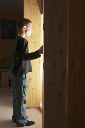 Boy opening a cupboard and bright lit illuminate him photo