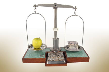 heavier: Traditional old style pharmacy scale with money heavier than yellow apple, small weights