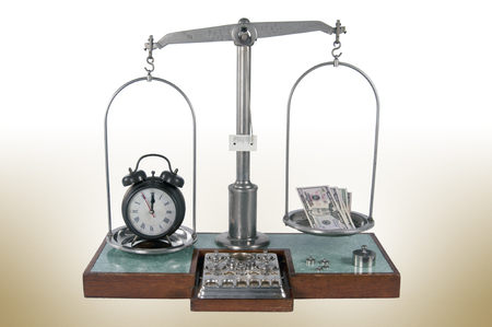 heavier: Traditional old style pharmacy scale with clock heavier than money, small weights Stock Photo
