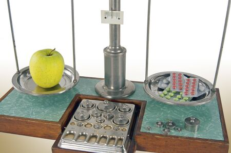 health care decisions: Traditional old style pharmacy scale balanced by yellow apple and drugs, small weights