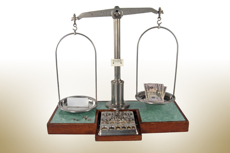 heavier: Traditional old style pharmacy scale with empty small white box heavier than money, small weights Stock Photo