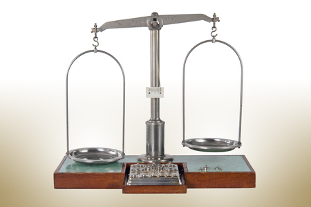 unbalanced: Traditional old style unbalanced pharmacy scale with empty pans, small weights