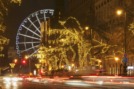 big wheel: Heavy traffic and a big wheel on background at night on a light string decorated street Stock Photo