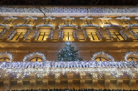 balcony door: Building facade with light string decoration at night with Christmas tree on the balcony, door and large window