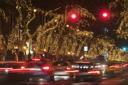 car lots: Heavy traffic at night on a light string decorated street