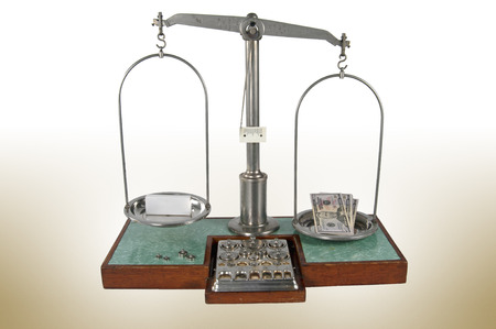 heavier: Traditional old style pharmacy scale with money heavier than empty small white box, small weights