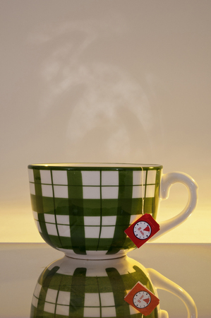 tea filter: A big steamy cup with tea filter on a mirror