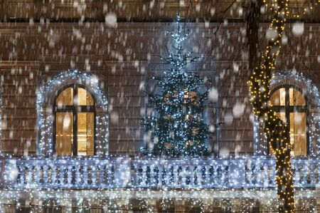 balcony door: Building facade with light string decoration at night with Christmas tree on the balcony, door and large window during snowfall