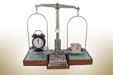 heavier: Traditional old style pharmacy scale with money heavier than clock, small weights Stock Photo