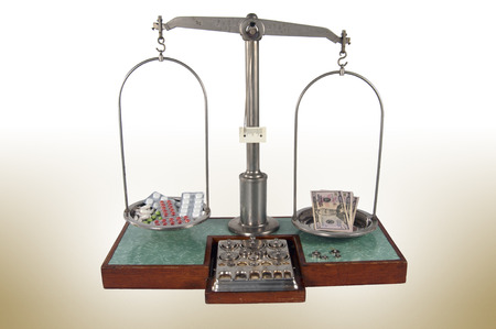 heavier: Traditional old style pharmacy scale with money heavier than drugs, small weights