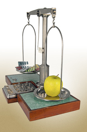 heavier: Traditional old style pharmacy scale with yellow apple heavier than drugs, small weights Stock Photo