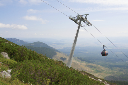 landscape mode: Cable car way on open hillside with pole and cabin Stock Photo