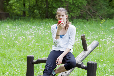 teeter: In a green grass park a young woman eating red apple and sitting on old teeter Stock Photo