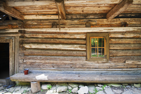 close p: Detailed time-honored old style chalet rough wood wall with tiny window, door and bench