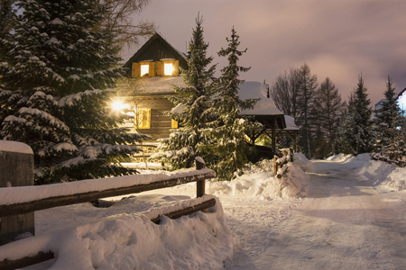 Evening lighted wooden house and road in the snowy village