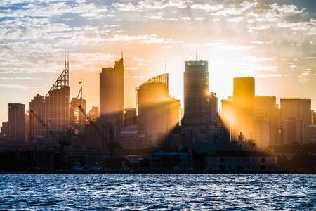 city of sunrise: Sun rays shining through the skyline of Sydney. Editorial