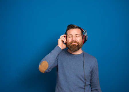 Young man over isolated blue wall listening to music with headphones