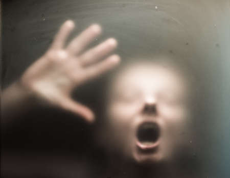 Scary picture of hands behind glass