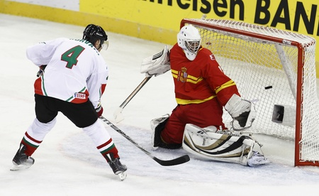 BUDAPEST - APRIL 22: Hungarian Andras Horvath (4) is scoring a goal, Spanish goalie Ander Alcaine is viewing the puck during Hungary vs. Spain (13:1) IIHF Division I/A World Championship at Budapest Sport Arena on April 22, 2011 in Budapest, Hungary.