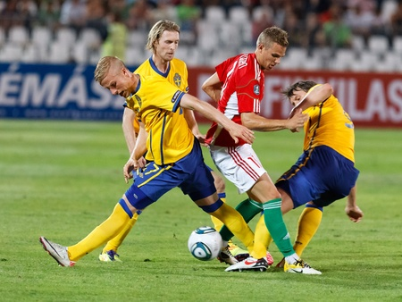 BUDAPEST - SEPTEMBER 2: Hungarian Vladimir Koman (in red) and Swedish Oscar Wendt (L), Christian Wilhelmsson and Kim Kallstrom (R) during Hungary vs. Sweden (2:1) UEFA Euro 2012 qualifying game at Puskas Stadium on September 2, 2011 in Budapest, Hungary.