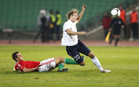 commits: BUDAPEST - November 14: Hungarian Roland Juh�sz (L) commits a foul against Norse Alexander Toft Soderlund during Hungary vs. Norway international friendly football game at Pusk�s Stadium on November 14, 2012 in Budapest, Hungary. Editorial