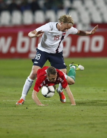 commits: BUDAPEST - November 14: Norse Havard Nielsen (18) commits a foul against Hungarian Vladimir Koman during Hungary vs. Norway international friendly football game at Pusk�s Stadium on November 14, 2012 in Budapest, Hungary. Editorial