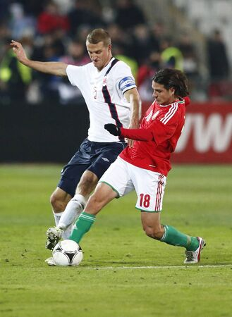 BUDAPEST - November 14:  Norse Brede Hangeland tries to make a tackle against Hungarian Imre Szabics (R) during Hungary vs. Norway international friendly football game at Pusk�s Stadium on November 14, 2012 in Budapest, Hungary.