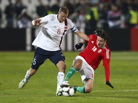 BUDAPEST - November 14: Hungarian Imre Szabics (R) tries to make a sliding tackle against  Norse Brede Hangeland during Hungary vs. Norway international friendly football game at Puskás Stadium on November 14, 2012 in Budapest, Hungary.