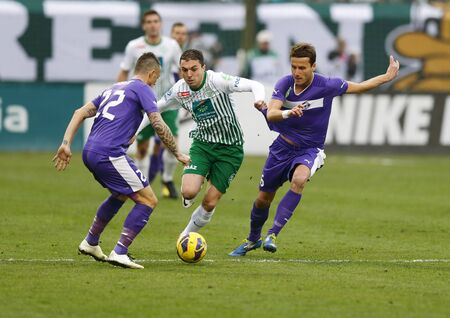 BUDAPEST - March 10: Vladan Cukic of FTC (M) runs with the ball between Kabat (L) and Dusan Vasiljevic (R) of UTE during Ferencvarosi TC (FTC) vs. Ujpest FC (UTE) OTP Bank League football game at Albert Stadium on March 10, 2013 in Budapest, Hungary.