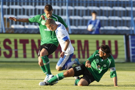 patrik: BUDAPEST - MAY 10: Patrik Vass of MTK (M) is tackled by Gabor Kovacs (L) and Laszlo Eger of Paks during MTK vs. Paks OTP Bank League football match at Hidegkuti Stadium on May 10, 2013 in Budapest, Hungary.