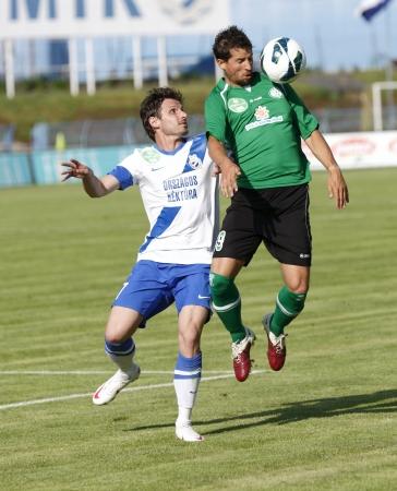 overtaken: BUDAPEST - MAY 10: Laszlo Zsidai of MTK (L) is overtaken by Laszlo Bartha of Paks during MTK vs. Paks OTP Bank League football match at Hidegkuti Stadium on May 10, 2013 in Budapest, Hungary.